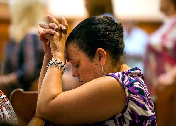 Wando Medina se arrodilla en oración durante la Misa.