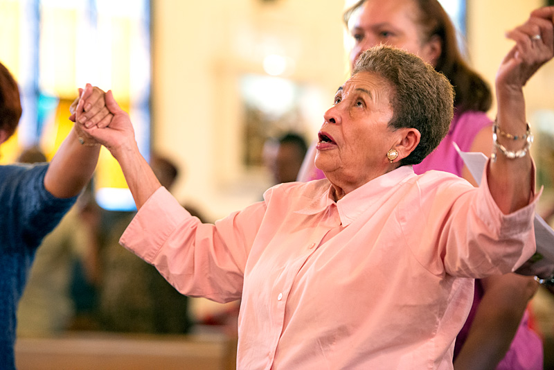 Gloria Pérez une sus manos con los congregantes en oración.