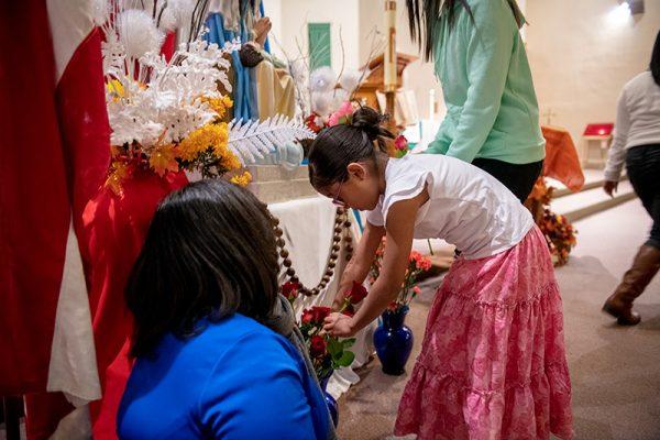 Danna Camila, de siete años, coloca una flor frente a la estatua.
