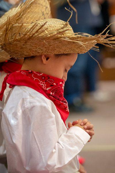 Keniel Valentín, de cinco años, se arrodilla en oración durante la Liturgia de la Eucaristía.