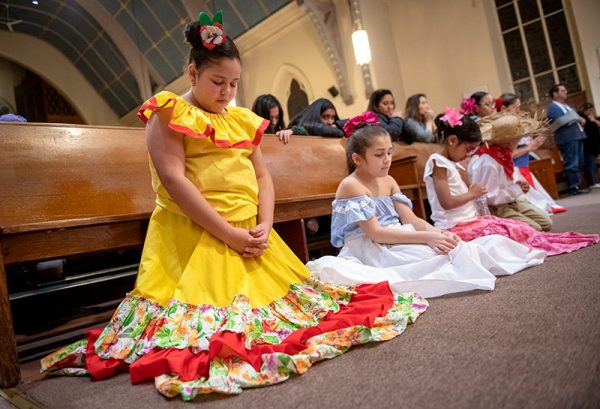Eight-year-old Ginerys Birrial kneels in prayer.