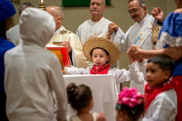 Keniel Valentín se toma de la mano con otros alrededor del altar durante la oración del Padre Nuestro.