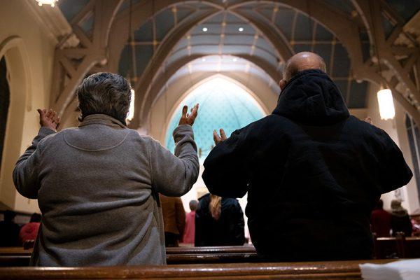 Los congregantes levantan sus manos en alabanza.