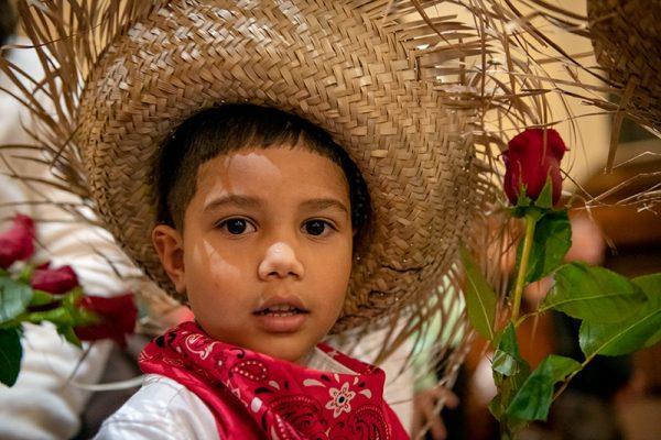 Santino Fachini, de cuatro años, se alinea para colocar una flor frente a la estatua de Nuestra Señora de la Providencia.