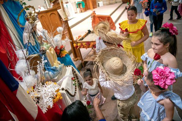 Los niños colocan flores frente a la estatua de Nuestra Señora de la Providencia.