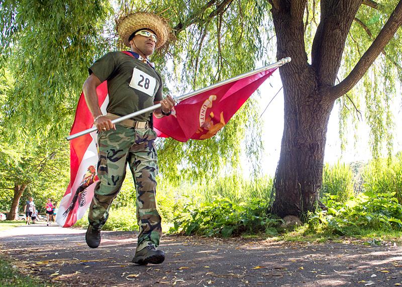 William Rodríguez lleva banderas puertorriqueñas y de la Marina durante la carrera.