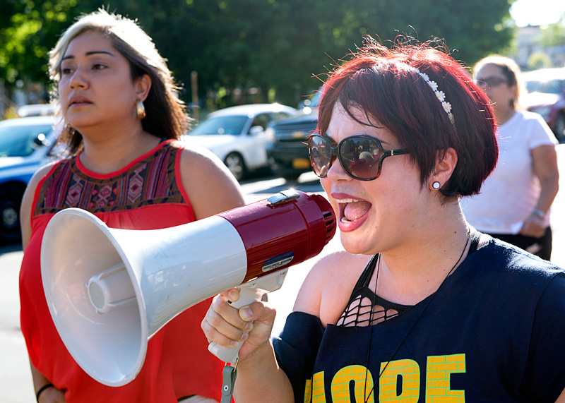 Sacha Ríos del Proyecto HOPE usa un megáfono para dirigir un canto de paz.