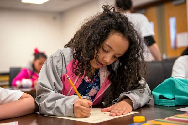 """Jaleah Lucas, de ocho años de edad, dibuja su concepto de una """"súper heroína"""" durante un taller para estudiantes de tercero a quinto grado."""
