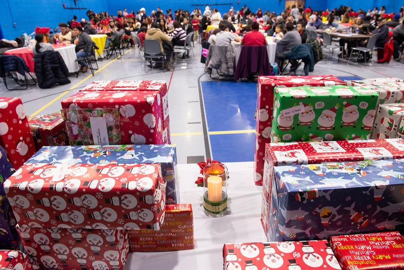 La gente come y espera la distribución de regalos por los Tres Reyes el 6 de enero durante la celebración del Consejo de Educación Bilingüe del Distrito Escolar de la Ciudad de Rochester en el Centro de Recreación David. F. Gantt.