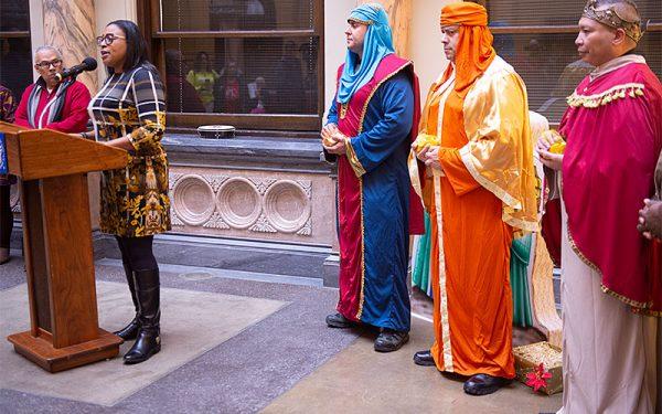 La Alcaldesa de Rochester, Lovely Warren, habla a la gente que se reunió para una celebración de los Reyes Magos en el Ayuntamiento de Rochester Tres miembros del Departamento de Policía de Rochester retrataron los reyes.