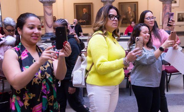 Mujeres toman fotos durante la celebración del día de los Tres Reyes en el Ayuntamiento de Rochester.