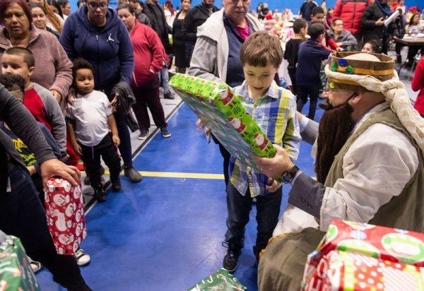 Un niño recibe su regalo desde uno de los Magos.