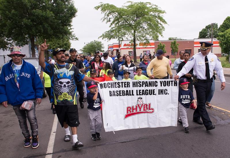 Los jugadores y los padres participan en el desfile de apertura de 2018 de la Liga de Béisbol Juvenil Hispana de Rochester.