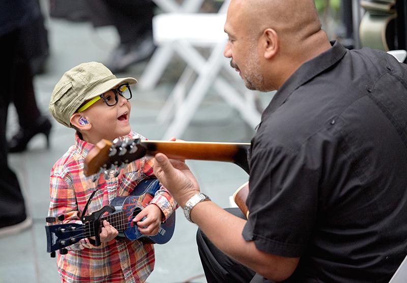 Julian Muños, de los 4 años, toca la guitarra con Orlando Nuñez que toca con el Conjunto Tipico.