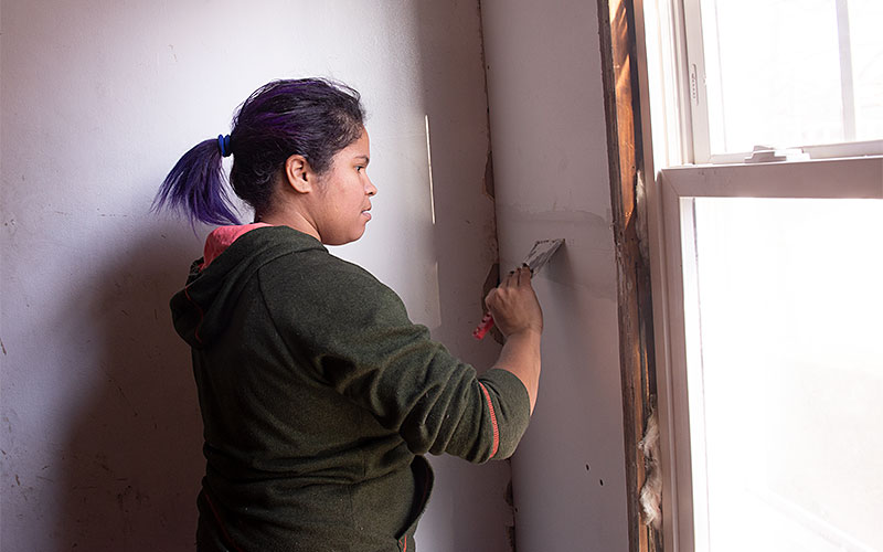 Ana H Martinez works to fini9sh dry walling a section of the stairway  at 228 Melville Street in Rochester on Nov. 26.as part of the City Roots Community Land Trust of Rochester.(EMC photo by John Haeger)