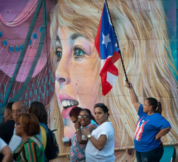 A woman holds a Puerto Rican flag.