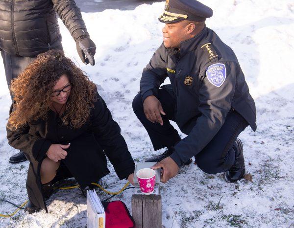 """Nancy Ortiz-Colón, la hermana del difunto official Manuel """"Manny"""" Ortiz, y el jefe de policía La'Ron D. Singletary accionaron el interruptor para iluminar el árbol de Navidad."""