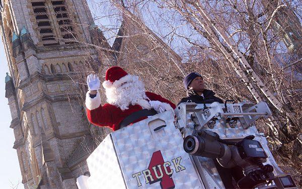 Papa Noel y el jefe de bomberos Will Jackson llegan para la ceremonia en un camión escalera.